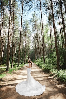 Młoda modelka kobieta w stylowej koronkowej sukni ślubnej, trzymając bukiet i pozowanie w lesie.