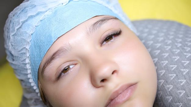 Młoda modelka leży na sofie kosmetologicznej z przedłużonymi rzęsami na jednym oku, wynik jest przed lewym i prawym okiem