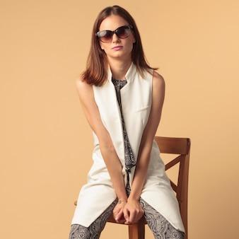 Młoda modelka moda siedzi na krześle na beżowym tle studio