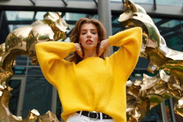 Młoda modelka pozuje na tle złotej rzeźby