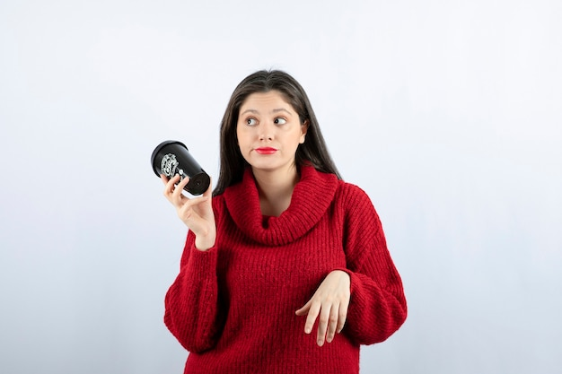 Młoda modelka w czerwonym swetrze trzymająca filiżankę kawy