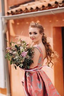 Młoda modelka w pięknej sukni z bukietem kwiatów na wsi we francji. dziewczyna z kwiatami na wiosnę wioska prowansji.