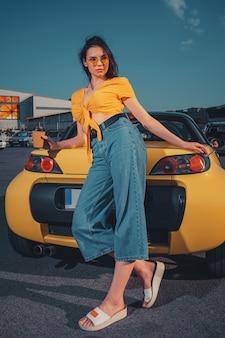 Młoda modelka w pomarańczowym topie niebieskich dżinsów i okularach przeciwsłonecznych trzyma papierowy kubek kawy opierając się na żółtym samochodzie na parkingu