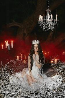 Młoda modelka w satynowej bieliźnie pozuje w wielkim gnieździe z czerwonym dymem i świecami na tle