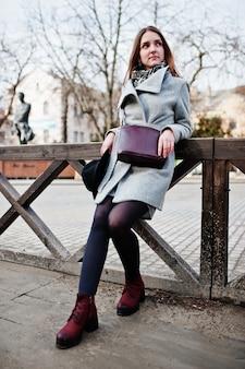 Młoda modelka w szarym płaszczu i czarnym kapeluszu ze skórzaną torebką na ramionach postawioną na drewnianych belkach na ulicy miasta.