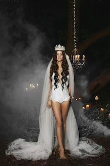 Młoda modelka z delikatnym makijażem w białej bieliźnie z koroną i welonem na głowie pozuje na zewnątrz w mglistym lesie