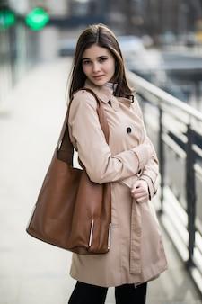 Młoda modelka z długimi włosami i brązową torbą spaceruje po centrum miasta