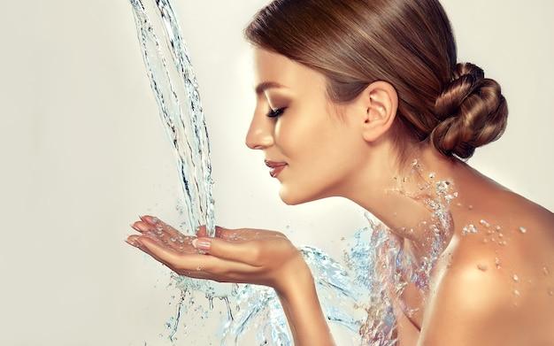 Młoda modelka z zamkniętymi oczami trzyma ręce pod wodą