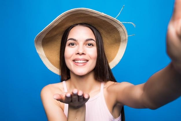 Młoda modna atrakcyjna dziewczyna w okularach przeciwsłonecznych i słomkowym kapeluszu wysyła pocałunek do kamery. miła figlarna i szczęśliwa kobieta z czerwonymi ustami na niebieskiej ścianie. z miejsca na kopię.