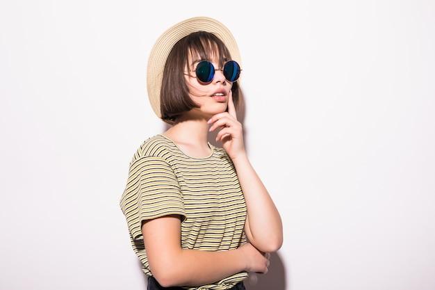 Młoda modna atrakcyjna hipster nastolatka w okulary i słomkowy kapelusz na białym tle.