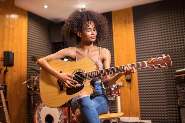 Młoda modna czarna dziewczyna z długimi kręconymi włosami siedzi gra na gitarze w studio nagrań z uśmiechem