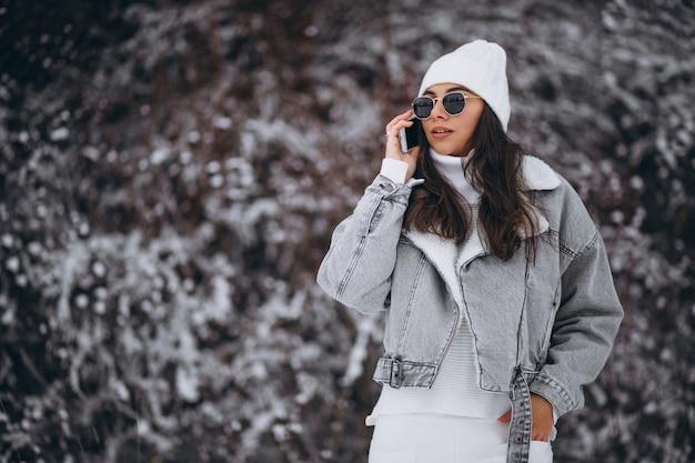 Młoda modna dziewczyna w zima parku używać telefon