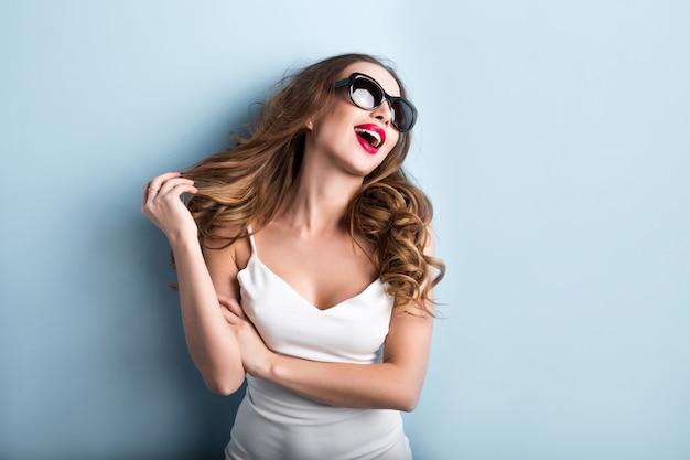 Młoda modna kobieta na błękitnym tle. emocje.