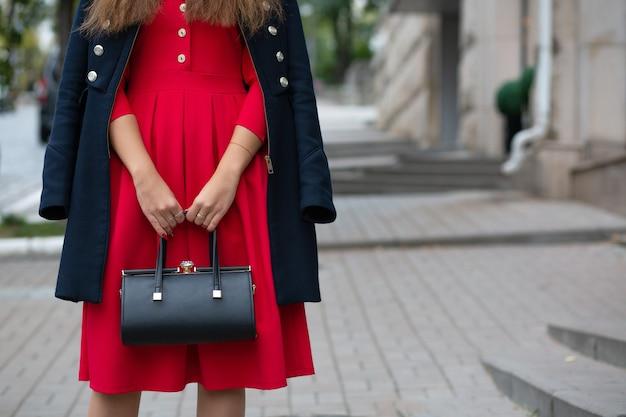 Młoda modna kobieta trzyma czarną skórzaną torebkę. pusta przestrzeń