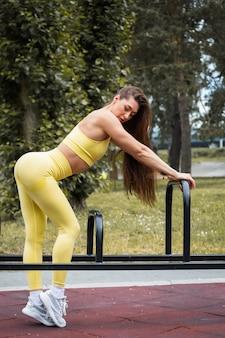 Młoda modna kobieta ubrana w żółte sportowe ubrania pozuje na boisku sportowym w parku