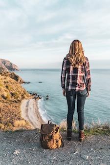 Młoda modna kobieta z plecakiem odkrywa wybrzeże w piękny dzień. pojęcie eksploracji i przygód