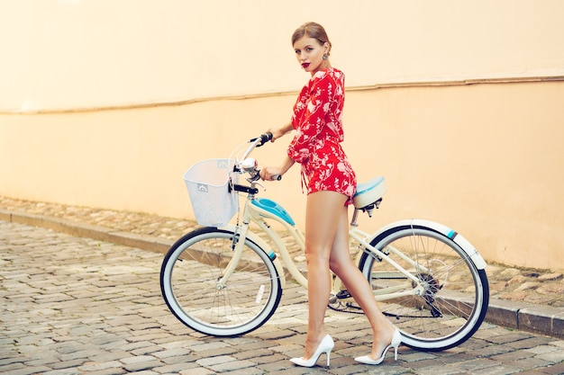 Młoda modna piękna seksowna dziewczyna w czerwonym garniturze latem w mieście na rowerze