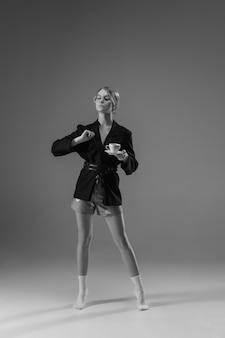 Młoda modna, stylowa kobieta ubrana w kurtkę i skarpetki pracująca w domu.