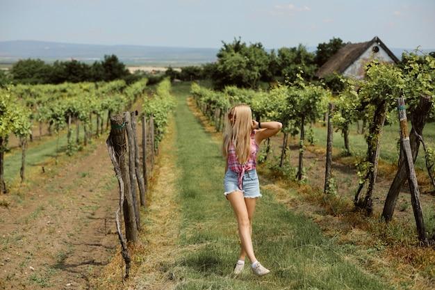Młoda modniś dziewczyna chodzi przez winnicy na wsi.