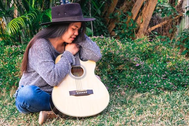 Młoda modniś kobieta bawić się gitarę w ogródzie