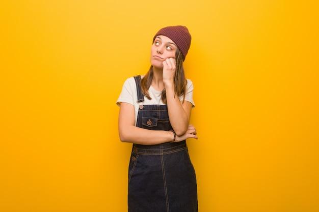 Młoda modniś kobieta myśleć coś, patrzeje z boku