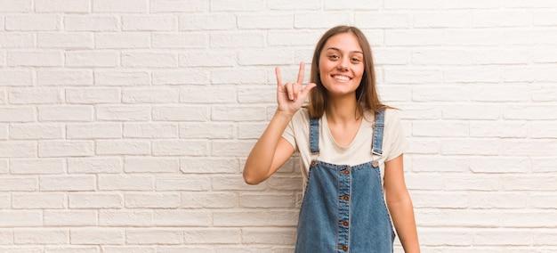 Młoda modniś kobieta robi rockowemu gestowi