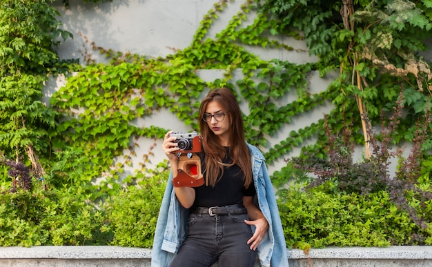 Młoda modniś kobieta w drelichowej kurtce i szkłach cieszy się ekranową retro kamerę na zewnątrz