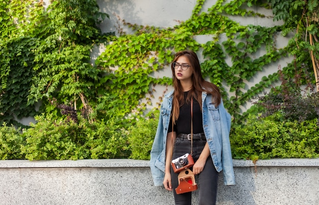 Młoda modniś kobieta w drelichowej kurtce, szkła z ekranową retro kamerą outdoors