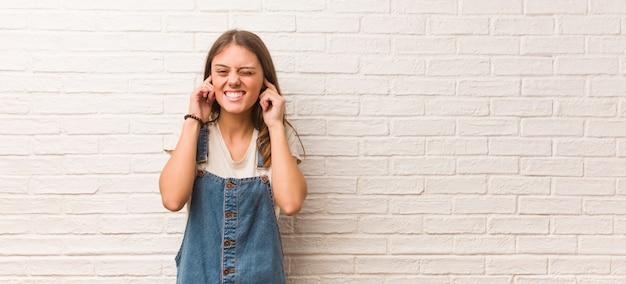 Młoda modniś kobieta zakrywa ucho z rękami