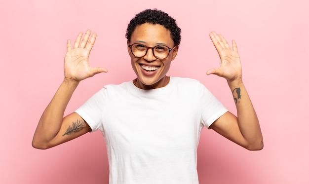 Młoda murzynka afro uśmiechnięta i wyglądająca przyjaźnie, pokazująca cyfrę dziesięć lub dziesiątą z ręką do przodu, odliczająca w dół