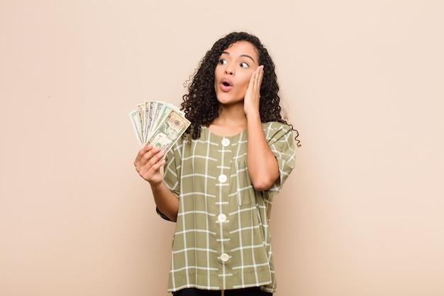 Młoda murzynka czuje się szczęśliwa, podekscytowana i zaskoczona, patrząc z boku obiema rękami na twarzy, trzymając banknoty dolarowe