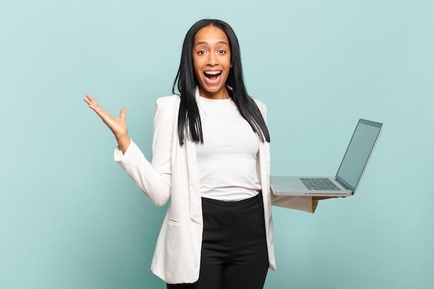 Młoda murzynka czuje się szczęśliwa, podekscytowana, zaskoczona lub zszokowana, uśmiechnięta i zdumiona czymś niewiarygodnym. koncepcja laptopa