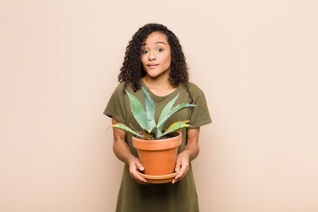 Młoda murzynka czuje się zdziwiona i zdezorientowana, wątpi, waży lub wybiera różne opcje z zabawnym wyrazem twarzy trzymającej kaktusa