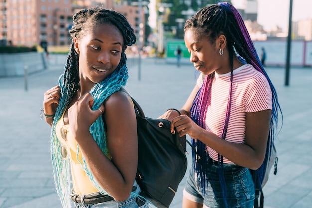 Młoda murzynka patrząc do swojej siostrzanej skórzanej torby i szukając czegoś