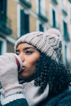 Młoda murzynka pije kawę wędruje po ulicach madrytu w zimie