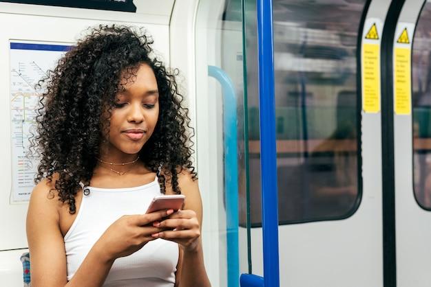 Młoda murzynka siedzi wewnątrz metra na telefonie komórkowym