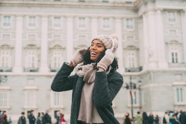 Młoda murzynka słucha muzyki i tanczy na telefonie komórkowym blisko pałac królewskiego w zimie
