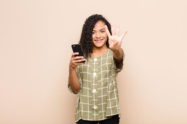 Młoda murzynka uśmiechnięta i wyglądająca przyjaźnie, pokazując numer cztery lub czwarty ręką do przodu, odliczając w dół ze smartfonem