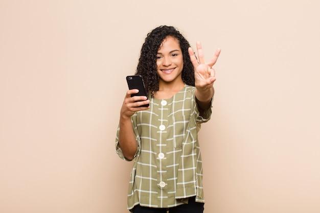 Młoda murzynka uśmiechnięta i wyglądająca przyjaźnie, pokazując numer trzy lub trzeci ręką do przodu, odliczając w dół ze smartfonem