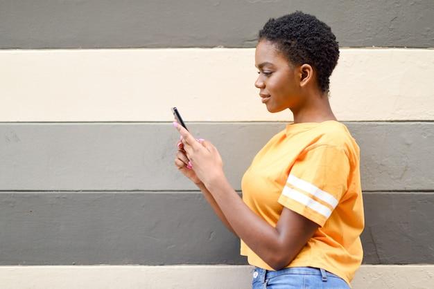 Młoda murzynka używa jej mądrze telefon outdoors