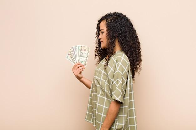 Młoda murzynka w widoku profilu, chcąc skopiować przestrzeń naprzód, myśląc, wyobrażając sobie lub marząc, trzymając banknoty dolarów