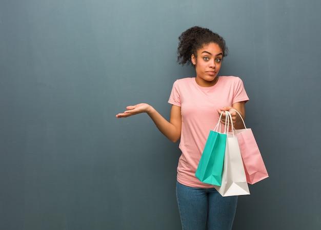 Młoda murzynka wątpi i wzrusza ramionami ona trzyma torby na zakupy