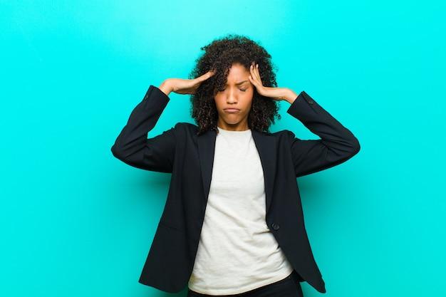 Młoda murzynka wygląda na zestresowaną i sfrustrowaną, pracuje pod presją bólu głowy i ma problemy z niebieską ścianą