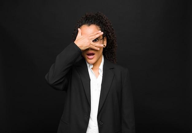 Młoda murzynka wyglądająca na zszokowaną, przestraszoną lub przerażoną, zakrywająca twarz dłonią i zerkająca między palcami na czarną ścianę