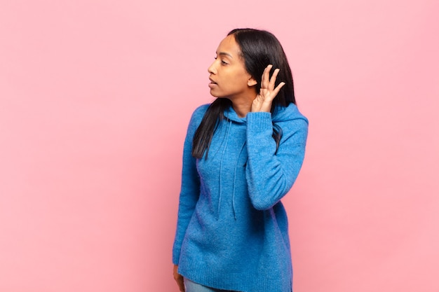Młoda murzynka wyglądająca poważnie i zaciekawiona, słuchająca, próbująca usłyszeć tajną rozmowę lub plotkę, podsłuchująca