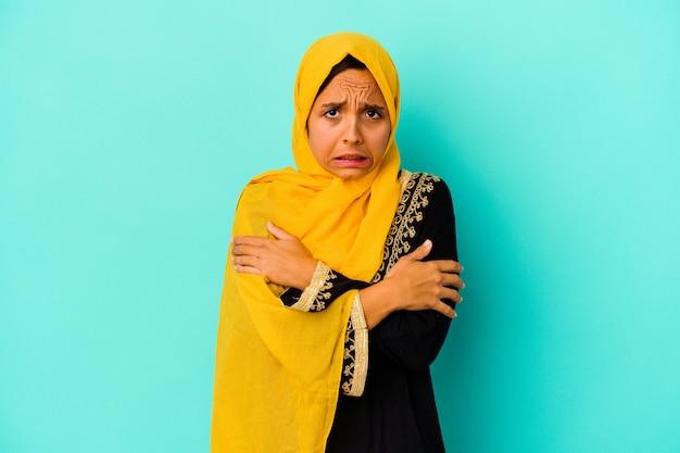 Młoda muzułmanka na niebiesko marznie z powodu niskiej temperatury lub choroby.