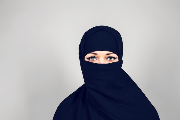 Młoda muzułmanka nosząca nikab na szarym tle