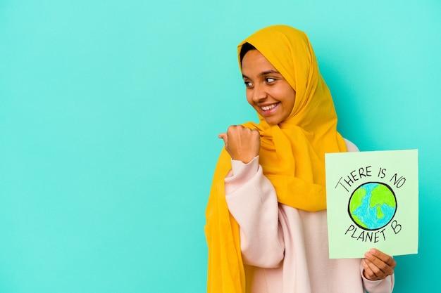 Młoda muzułmanka trzyma a nie ma afisz planety b na białym tle na niebieskim tle wskazuje palcem kciuka, śmiejąc się i beztrosko.
