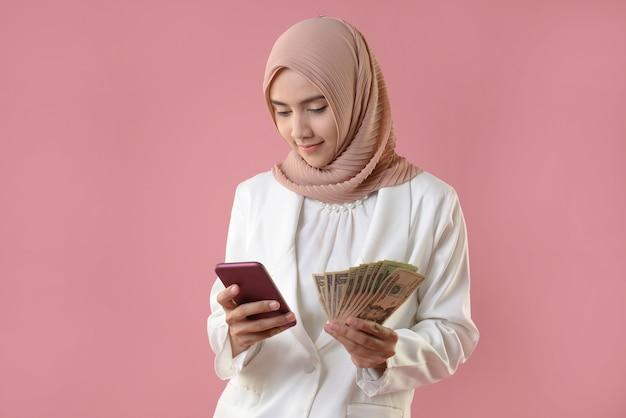 Młoda muzułmanka trzymać pieniądze i smartphone