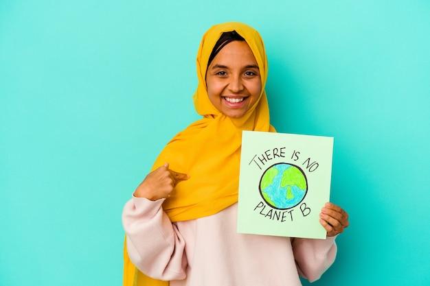 Młoda muzułmanka trzymająca a nie ma afisz planety b na białym tle na niebieskim tle osoba wskazująca ręcznie na miejsce na koszulkę, dumna i pewna siebie